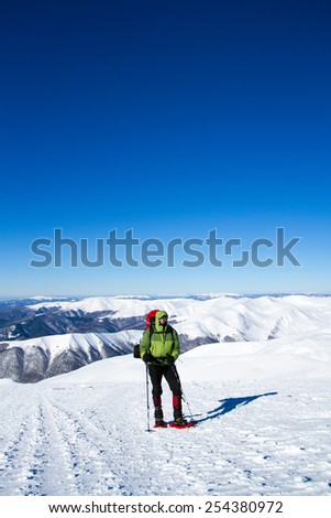 Winter hiking in the mountains on snowshoes with a backpack and tent. #254380972