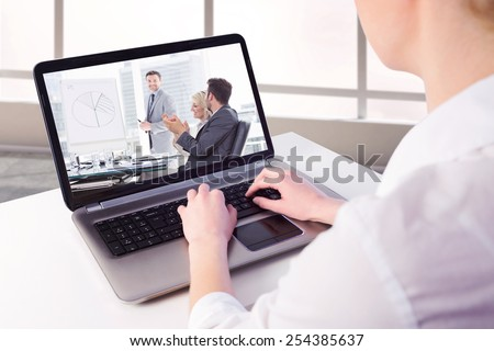 Businesswoman using her laptop against business people in office at presentation #254385637