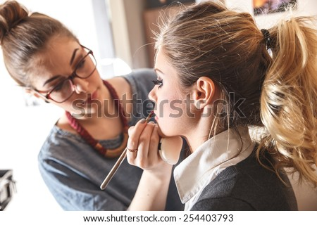 Make-up artist work on her friend.Real people. Royalty-Free Stock Photo #254403793