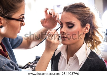 Make-up artist work on her friend.Real people. Royalty-Free Stock Photo #254403796