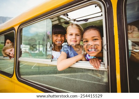 Cute pupils smiling at camera in the school bus outside the elementary school #254415529