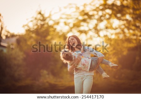 Mother and little daughter playing together in a park Royalty-Free Stock Photo #254417170