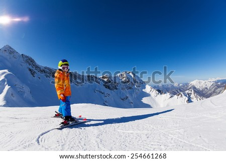 Boy skiing in sunny weather with mountain view #254661268