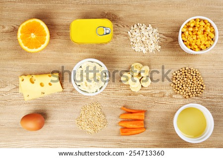 Various food products containing vitamins on wooden background #254713360