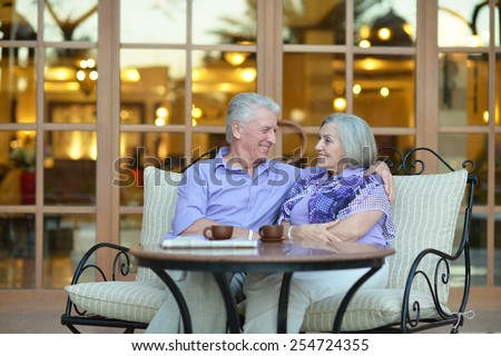 Senior couple drinking coffee outside at the resort during vacation #254724355