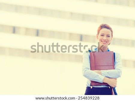 portrait of confident smiling happy pretty young professional woman standing on a background of corporate city office. Positive face expression  #254839228