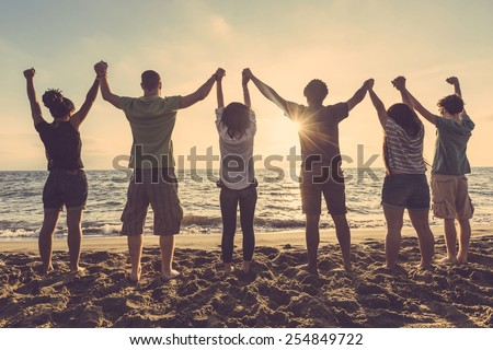 Multiracial group of people with raised arms looking at sunset. Backlight shot. Happiness, success, friendship and community concepts. Royalty-Free Stock Photo #254849722