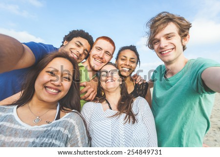 Multiracial group of friends taking selfie at beach. One girl is asiatic, two persons are black and three are caucasian. Friendship, immigration, integration and summer concepts. Royalty-Free Stock Photo #254849731