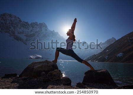 Young woman is practicing yoga at mountain lake #254850970