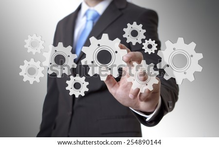 Businessman playing with gears and various cogwheels #254890144