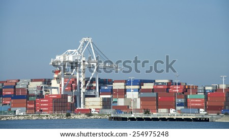 OAKLAND, CA - FEBRUARY 20, 2015: Thousands of backlogged shipping containers remain stacked at the Port of Oakland waiting to be transported by truck, rail or cargo ship.  #254975248