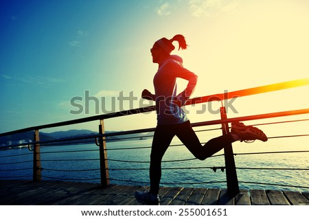 healthy lifestyle sports woman running on wooden boardwalk sunrise seaside  Royalty-Free Stock Photo #255001651