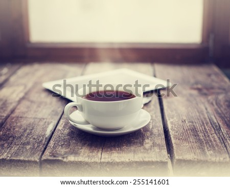 Digital tablet and cup of coffee on old wooden desk. Simple workspace or coffee break in morning/ selective focus #255141601