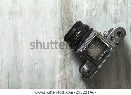 Old medium format camera and films on vintage wooden table