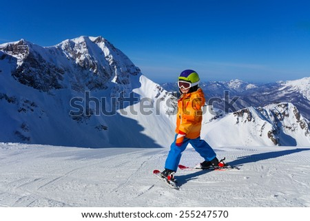 Boy in mask skiing with beautiful mountain view #255247570