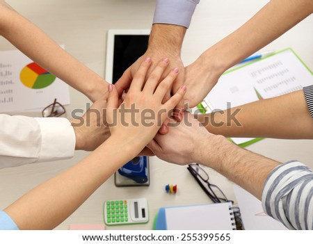 United hands of business team on workspace background top view #255399565