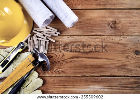 hammer, protective gloves, folding ruler, model knife, blueprint, wooden dowels and yellow safety helmet on wooden background #255509602