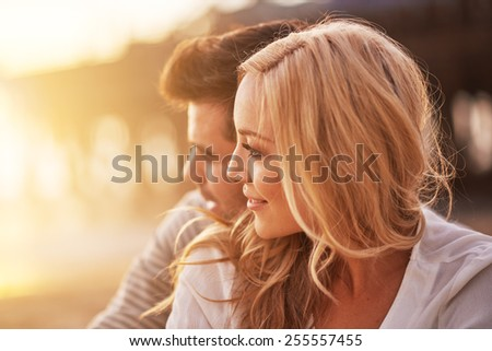 pretty girl cuddling with boyfriend on beach at santa monica with shallow depth of field and bright warm lens flare #255557455