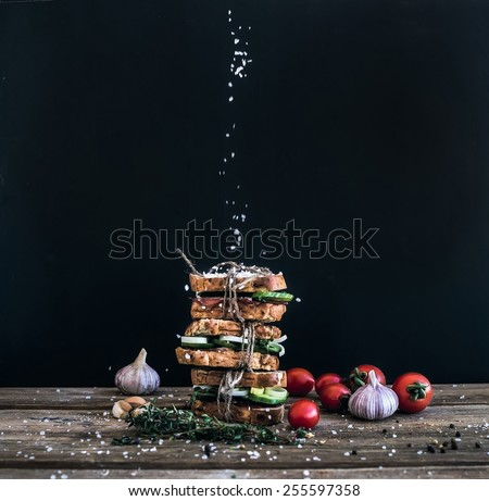 Sandwiches with smoked meat, cucumber and herbs tied with a rope, placed one over another. Salt is being strewed on them from above on them  #255597358