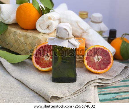 A glass bottle of blood orange oil. Spa products in the background. #255674002