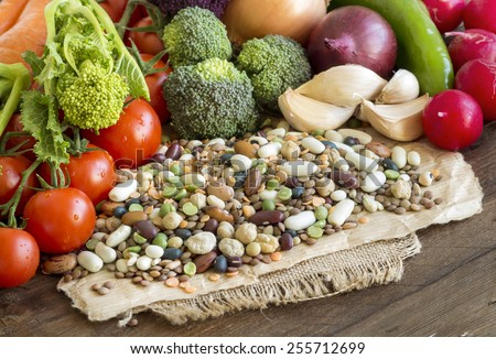Mixed legumes and vegetables on a wooden table #255712699