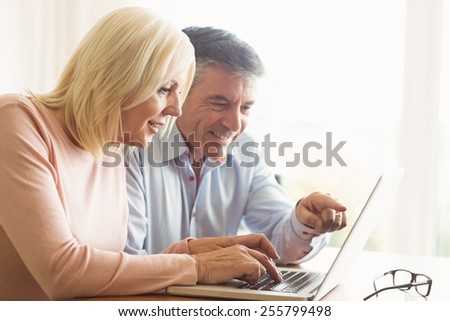 Happy mature couple using laptop at home in the kitchen #255799498