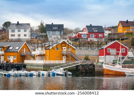 Norwegian fishing village, wooden houses on the sea coast and moored boats #256008412