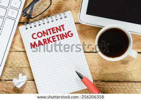 Notebook with content marketing. Workplace with keyboard , tablet pc , coffee, notebook with content marketing and pen on wood table