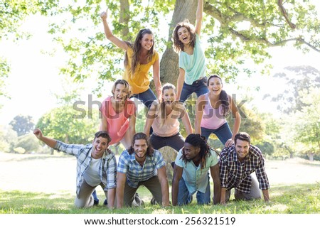 Happy friends in the park making human pyramid on a sunny day #256321519