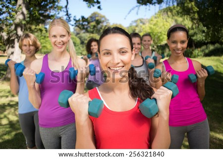 Fitness group lifting hand weights in park on a sunny day #256321840