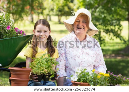 Happy grandmother with her granddaughter gardening on a sunny day #256323694