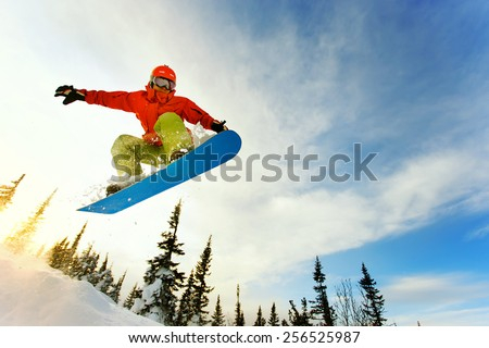 Snowboarder jumping through air with deep blue sky in background #256525987