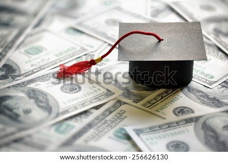 Graduation mortar board cap on one hundred dollar bills concept for the cost of a college and university education