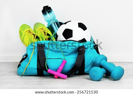 Sports bag with sports equipment in room Royalty-Free Stock Photo #256721530