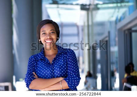 Portrait of a happy young business woman standing outside office building #256722844