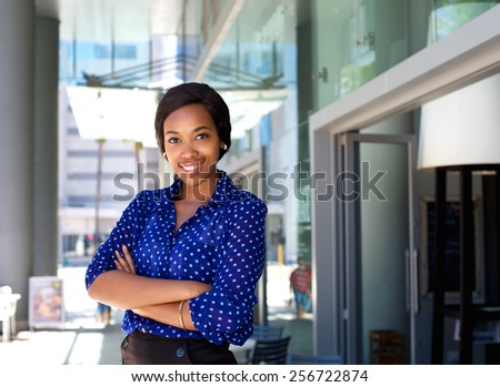 Portrait of a friendly smiling business woman standing outside in the city #256722874