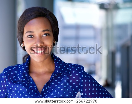 Close up portrait of a happy business woman smiling outside office building #256722970