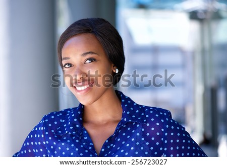 Close up portrait of a friendly young business woman standing outside office building #256723027