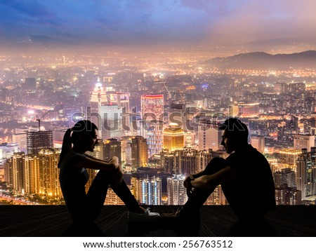 Silhouette of young couple face to face sit on ground in the city night. #256763512