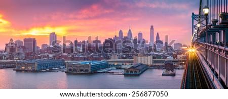 Philadelphia panorama under a hazy purple sunset. An incoming train crosses Ben Franklin Bridge.