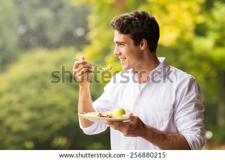 handsome young man eating scrambled egg for breakfast #256880215