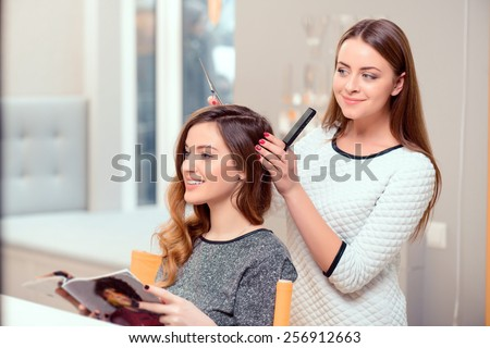 Going for a change of style. Young beautiful woman discussing hairstyling with her hairdresser holding a comb and scissors while sitting in the hairdressing salon #256912663
