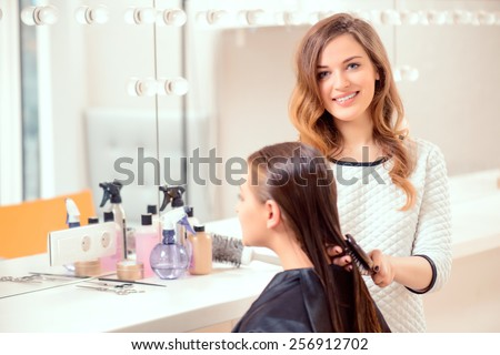 I love my job. Beautiful hairdresser doing hairstyle to her client and smiling at camera while standing on the background of a professional hairdressing salon #256912702