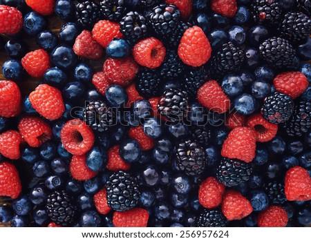 blueberries, raspberries and black berries shot top down Royalty-Free Stock Photo #256957624
