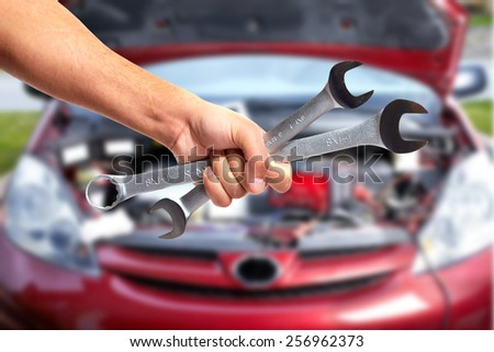 Hand of car mechanic with wrench. Auto repair garage. #256962373