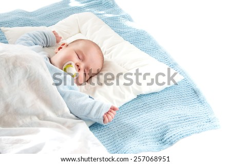 Four month old baby sleeping on blue blanket on white bavkground #257068951