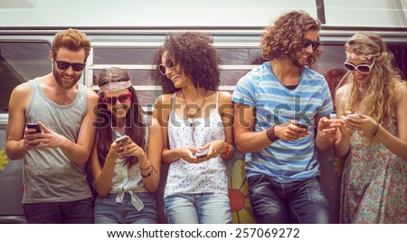 Hipster friends using their phones on a summers day Royalty-Free Stock Photo #257069272