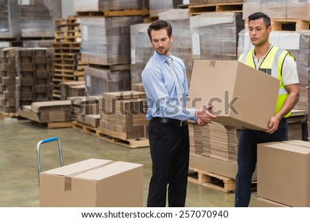 Warehouse worker and manager carrying a box together in a large warehouse #257070940