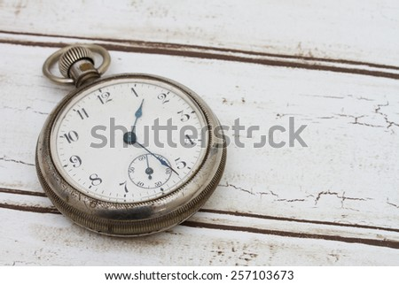 Old pocket watch on a grunge wood background #257103673