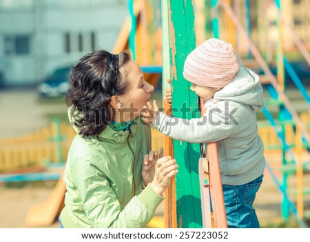 Mother and daughter playing on the playground outdoors on a sunny day #257223052